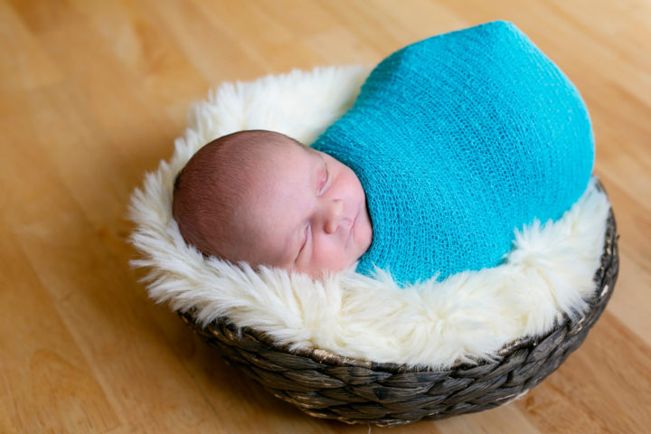 A new baby wrapped in a turquoise wrap in a wicker basket