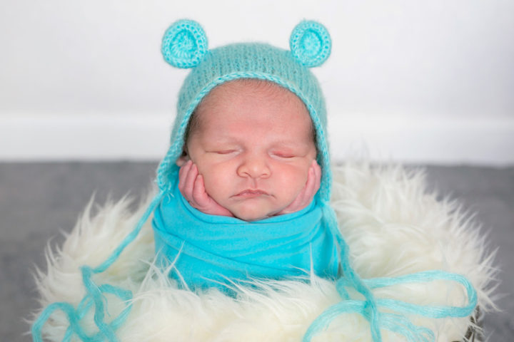 A new baby in a turquoise hat and warp in a basket