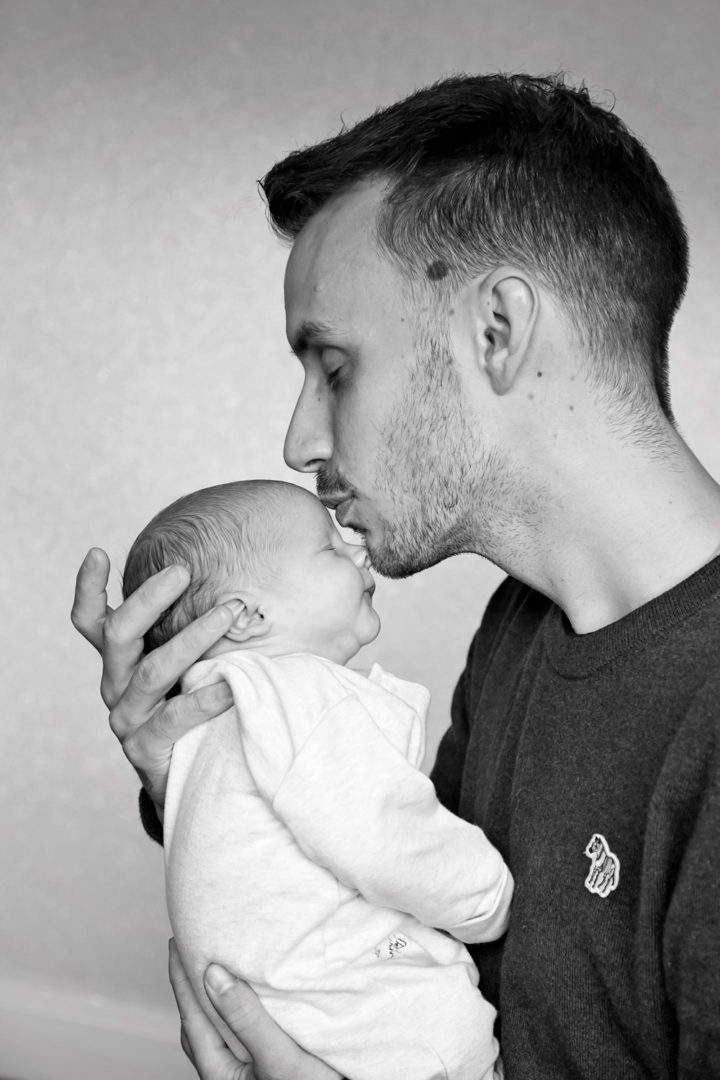 A father kissing his new baby on the forehead